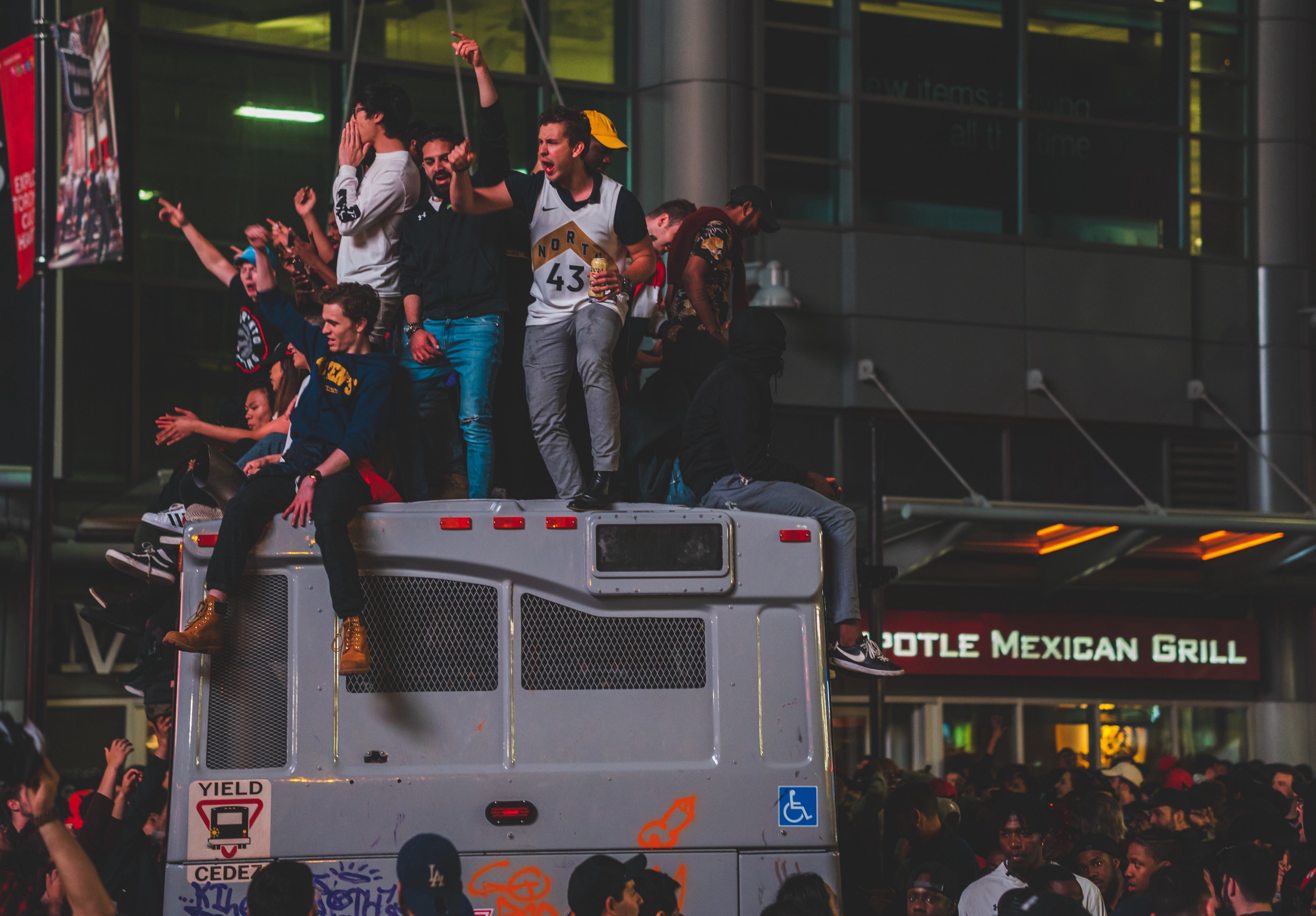 A mob on a street, sitting on top of a bus, gesturing etc.