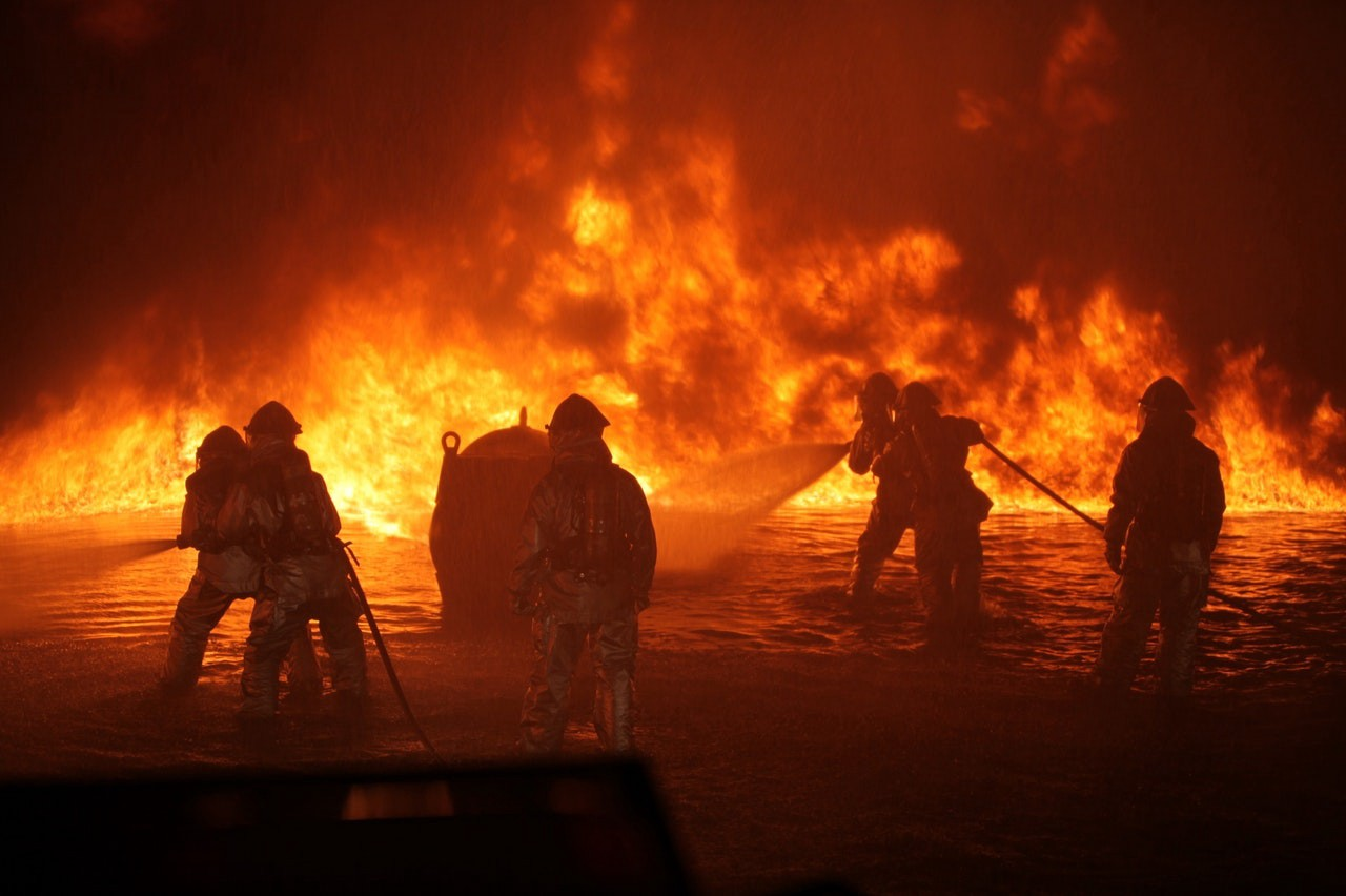 Firefighters silhouetted against a backdrop of flames.