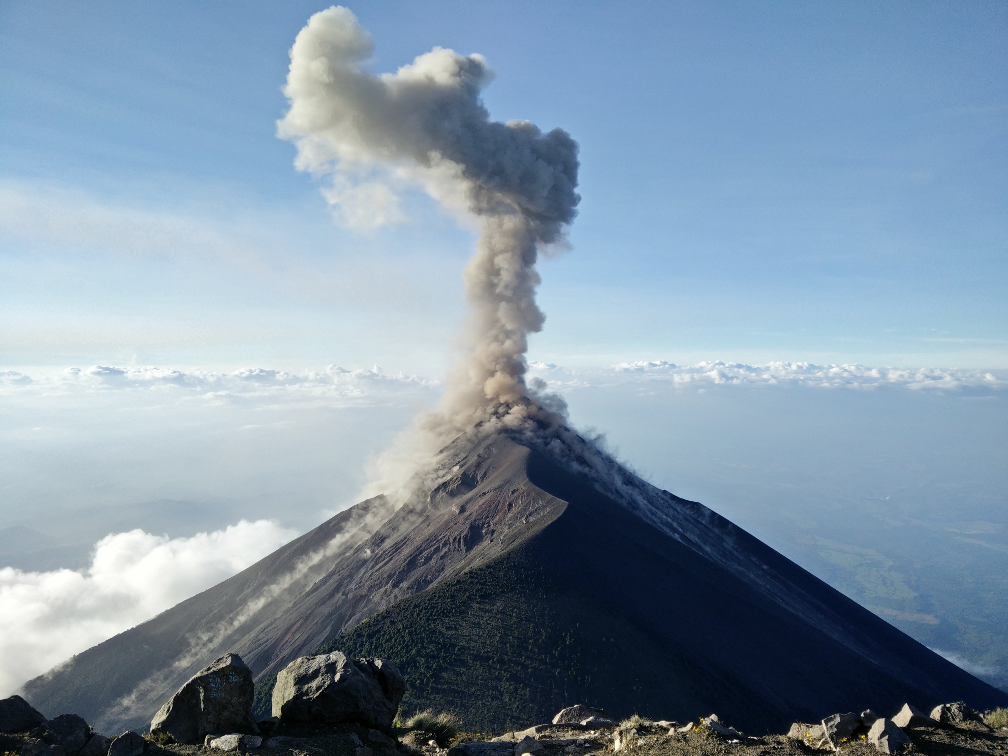 A conical volcano emitting gas and smoke from its tip.